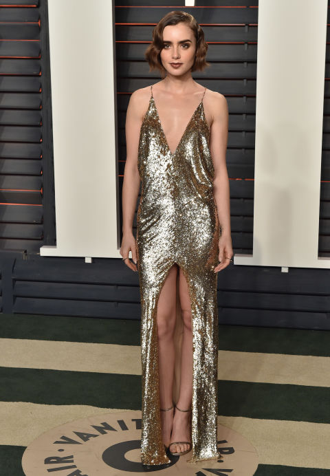 Lily Collins wore a gold Saint Laurent dress to attend the 2016 Oscars Vanity Fair party.